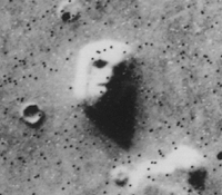 A satellite photo of a mesa in Cydonia, often called the Face on Mars. Later imagery from other angles did not contain the illusion. Image from Wiki.