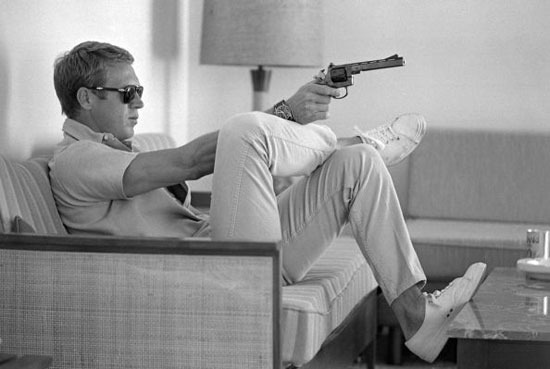 The King of Cool even looks cool threatening someone with a gun. Image from chasingstevemcqueen.tumblr.com