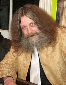 Hopefully, with better hair though. Alan Moore from the wiki linked above.