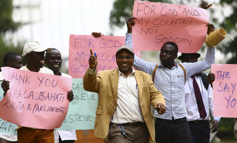 Ugandan anti-gay activist Pastor Martin Ssempa (C) leads anti-gay supporters as they celebrate after Uganda's President Yoweri Museveni signed a law imposing harsh penalties for homosexuality in Kampala on Feb.24, 2014. Reuters/Edward Echwalu